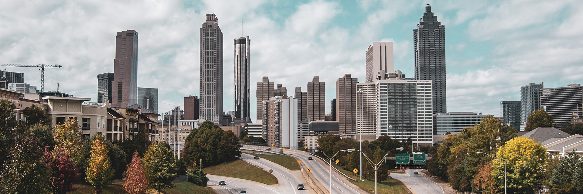 The Atlanta skyline with a highway leading towards the buildings.